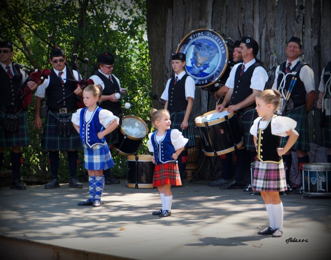Girls in kilts dancing to the music of Scottish bagpipes and drums at Michigan Renaissance Faire.