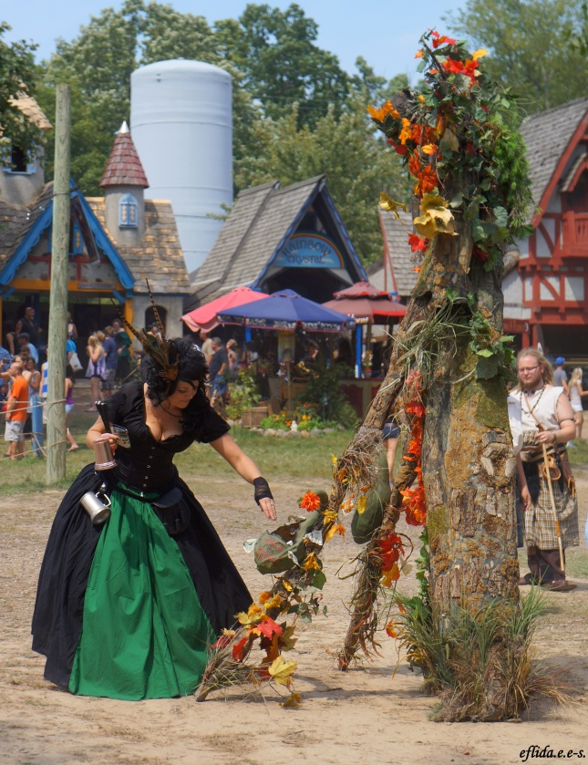 A lady giving coins to an ent at Michigan Renaissance Faire in Holly, Michigan.