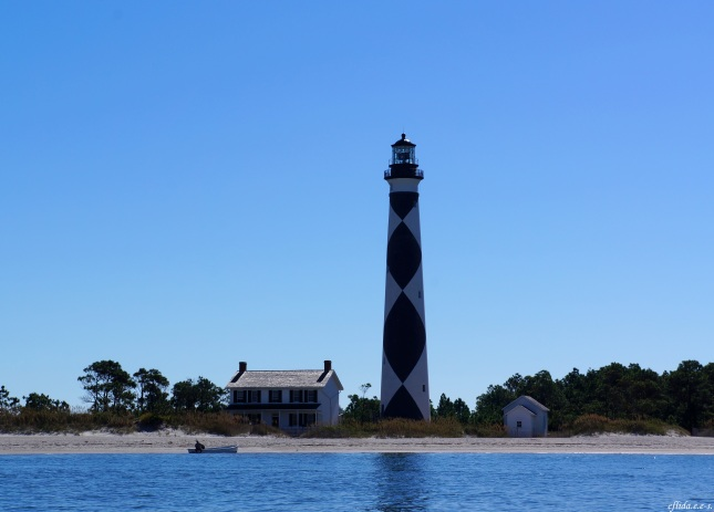 The view approaching the Cape Lookout Lighthouse in Southern Outer Banks, North Carolina with the asst. keeper's house on the left and the oil shack on the right. In this photo, we can see the black diamonds, therefore we are sailing in north-south direction.