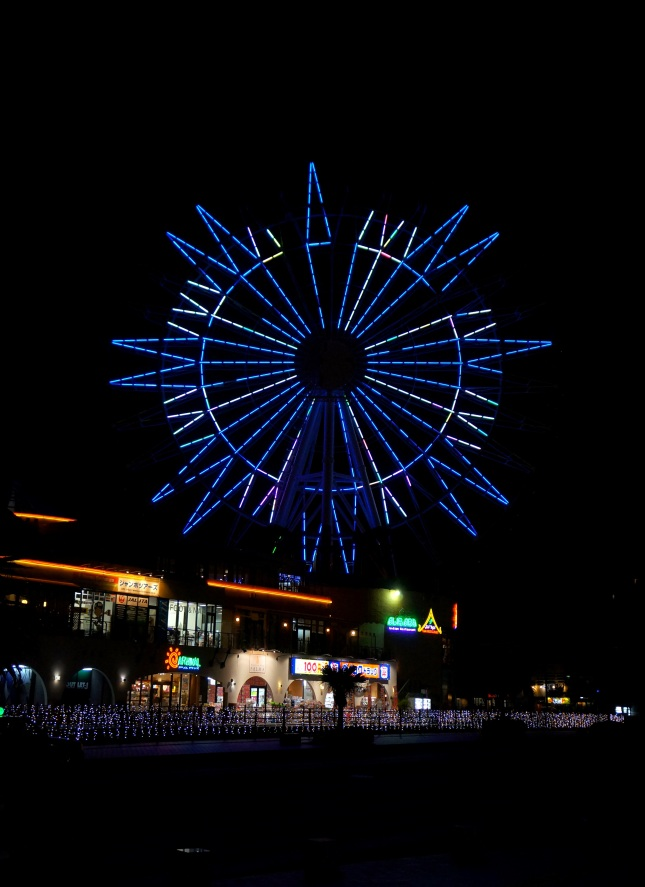 The ferris wheel lit at night in Mihama American Village in Chatan, Okinawa, Japan.