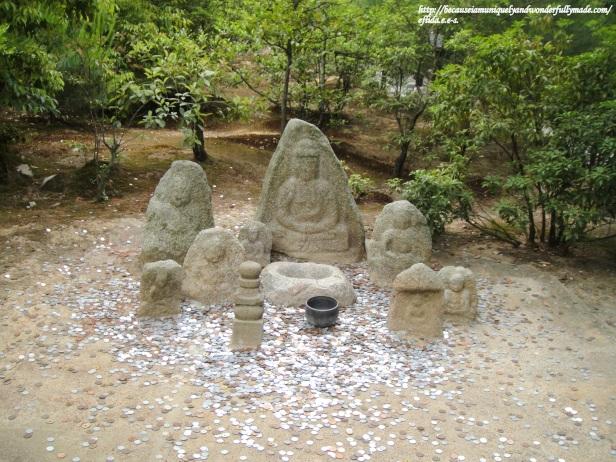 Statues for coin toss inside Kinkaku-ji in Kyoto, Japan.