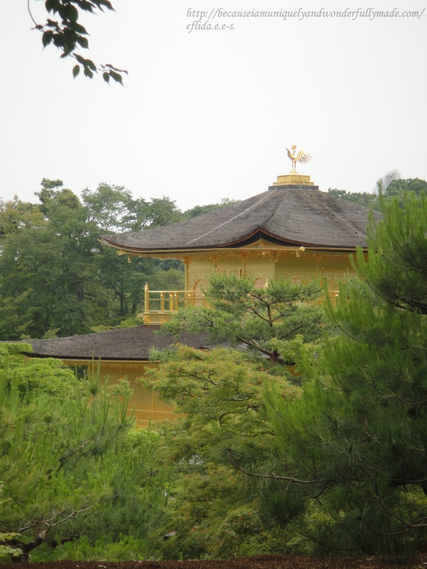 A peak of the third and topmost floor of Kinkaku whic is in Chinese Zen style capped with a golden phoenix.