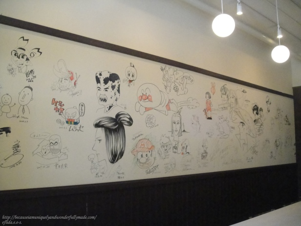 Wall of illustrations at Kyoto International Manga Museum Cafe.