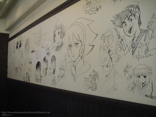 Wall of illustrations at Kyoto International Manga Museum Cafe.