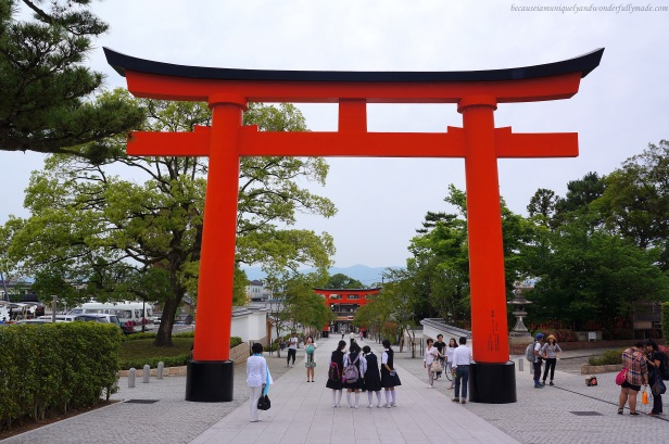 Giant torii painted in red-orange hue leads to the front of the Romon Gate at Fushimi Inari Taisha 伏見稲荷大社 in Kyoto, Japan.