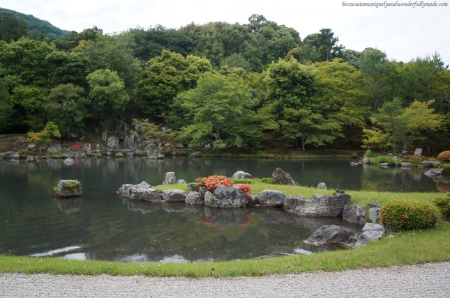 The garden featuring Sogen-chi pond (曹源地) surrounded by rocks, pine trees, maple trees and mountains at Tenryu-ji Temple in Arashiyama district in Kyoto, Japan.