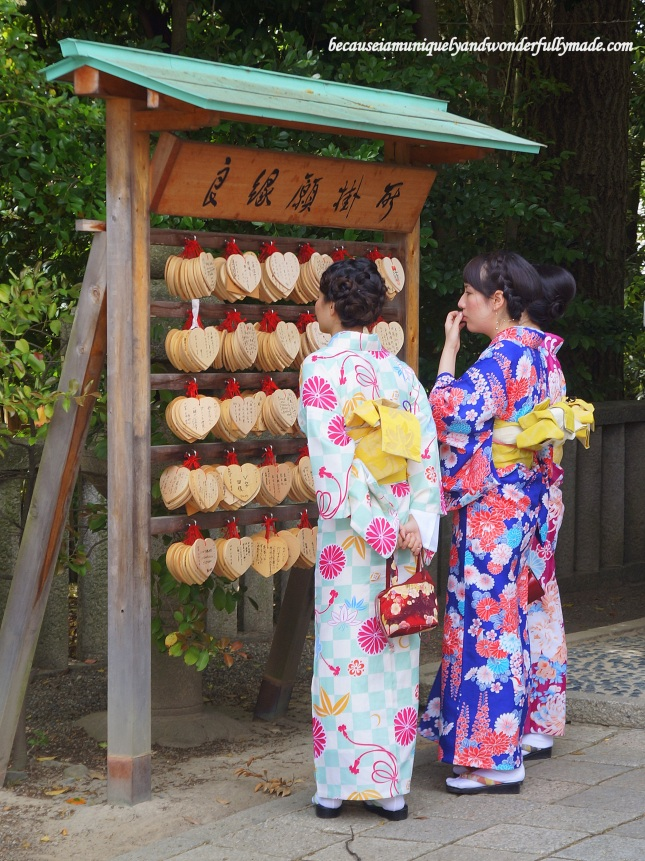 Beautiful Japanese women dressed in summer kimono trying to choose which 'ema' plaque to write their beauty wishes on at Utsukushi-gozensha 美御前社at Yasaka Shrine 八坂神社in Kyoto, Japan.