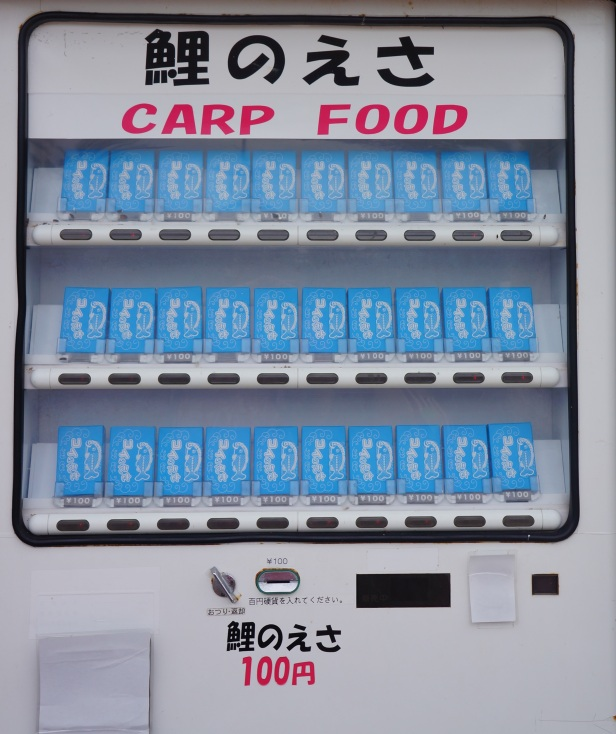 Fish food in boxes are available on a vending machine at 100 yen for koi and carp feeding at the Water Park in Southeast Botanical Garden in Okinawa City, Okinawa, Japan. (東南植物楽園 Tōnan Shokubutsu Rakuen)
