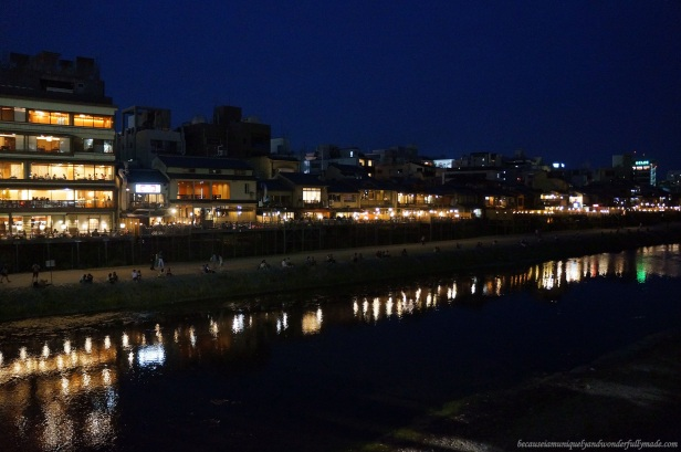 The beautiful Kamo River 鴨川 lined with romantically-lit restaurants viewed over at  Shijo Ohashi 日本語 in Kyoto, Japan.