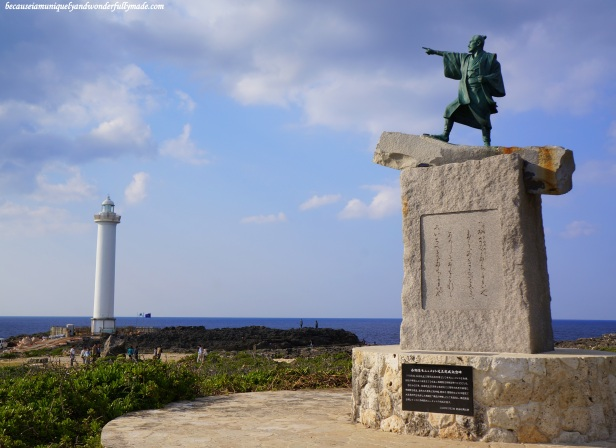 Cape Zanpa Lighthouse in Yomitan, Okinawa, Japan. The statue on the right is Taiki, the first man from Okinawa to be sent to China to establish a tribute trade.