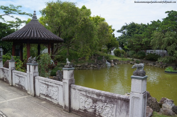 The pond and gazebo and some parts of the small bridge with Chinese animals signs at Fukushuen Garden 福州園 in downtown Naha 那覇市 Okinawa 沖縄本島,  Japan 日本国.