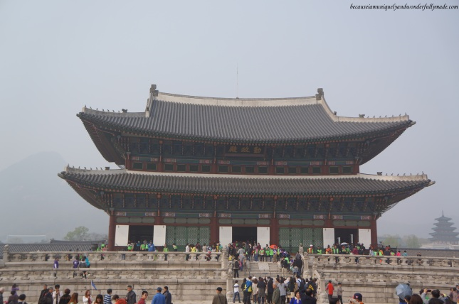 Full view of Geunjeongjeon Hall 근정전 and a gathering tourists at Gyeongbokgung Palace 경복궁 in Seoul, South Korea.