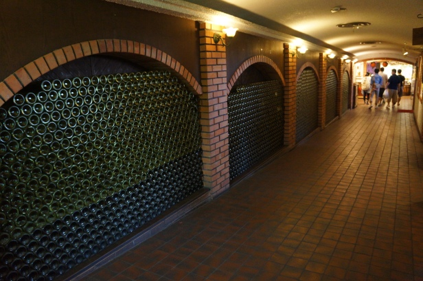 Wall of empty wine bottles at Nago Pineapple Park in Okinawa, Japan.